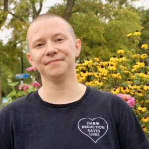 """headshot of white trans-masculine human in front of flowers, wearing a black t-shirt that reads """"Harm Reduction Saves Lives"""""""